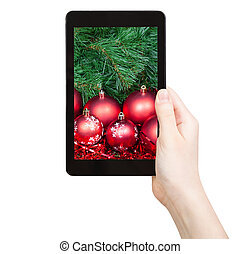 hand holds tablet pc with red Xmas baubles