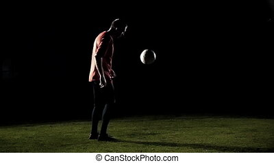 Soccer Player Juggling A Ball Black Background Slow Motion -...