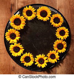 Round border of colorful yellow sunflowers arranged around...
