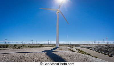 Wind turbine against sun and windmill farm - Closeup of...