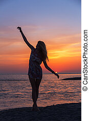 Beautiful young woman on the beach at sunset