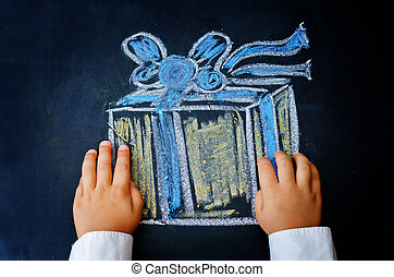 childrens hands holding a gift drawn with chalk on a black...
