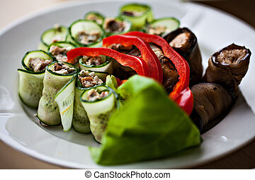 White plate of vegetable snacksEggplant cucmber Rolls with...