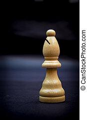 Bishop, wooden chess piece isolated on dark background