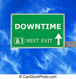 DOWNTIME road sign against clear blue sky