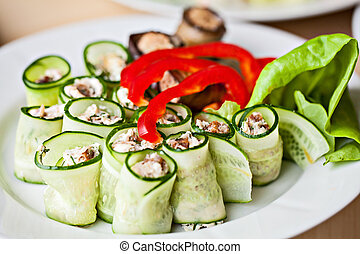 White plate of vegetable snacks.Eggplant cucmber Rolls with...