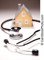 Stethoscope and Model House on Gradated Background with...