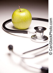 Stethoscope and Green Apple on Gradated Background with...