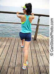 fitness sports woman runner stretching on wooden boardwalk...