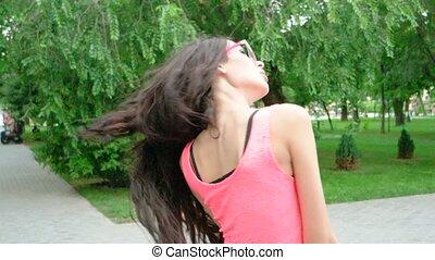 young beautiful long curly hair woman dancing outdoors