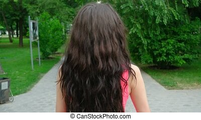 young beautiful long curly hair woman dancing outdoors.