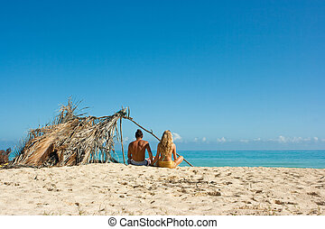 Couple on the beach - Two lovers near their shelter on the...
