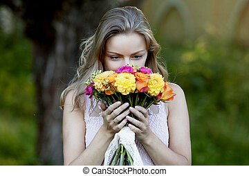 Young beautiful woman with a bright bouquet, girl smelling...
