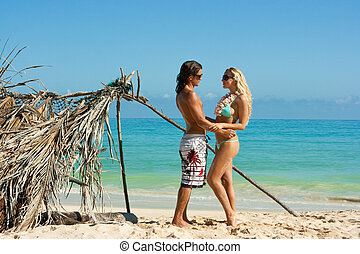 Couple on the beach - Girl and boy at their shelter on the...
