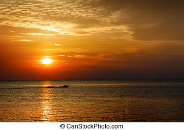 Silhouette of a man on a jet ski in the sea at sunset The...