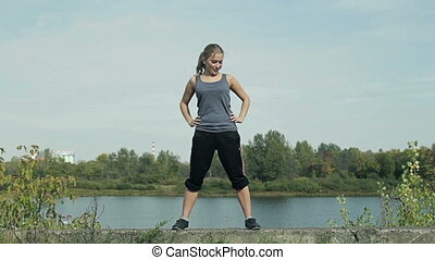 Young girl doing sport exercises on the street