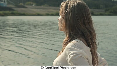 close up of a girl looking at the river and into the camera