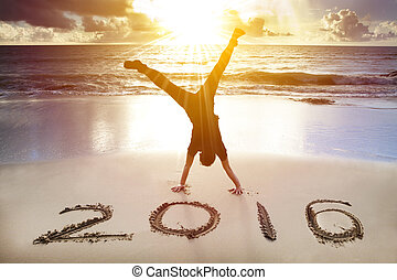 happy new year 2016. young man handstand on the beach