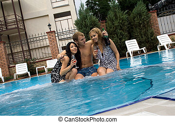 Young man and two girls drink champagne in pool