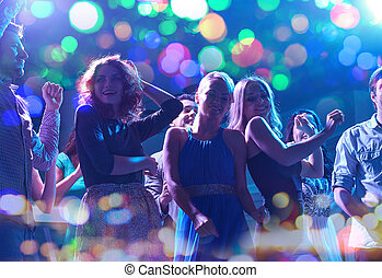 group of happy friends dancing in night club - party,...