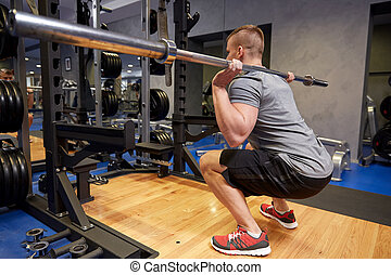 young man flexing muscles with bar in gym - sport, fitness,...