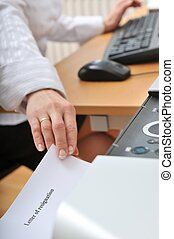 Hand reaching resignation letter from printer - Hand of...