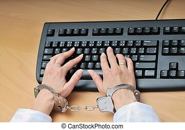 Hands tied with handcuffs on keyboard - Hands tied with...