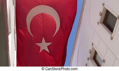 Big Turkish flag flying above the houses on the background...