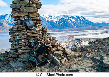 Rifle and snow shoes overlooking Longyearbyen city,...