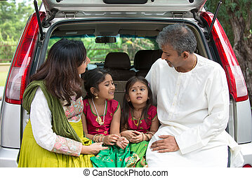 Happy Asian Indian family sitting in car talking and smiling happily
