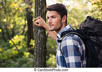 Man traveling in forest - Portrait of a young man traveling...