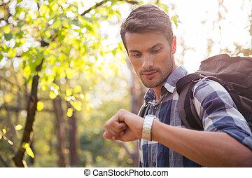 Male hiker looking on wrist watch
