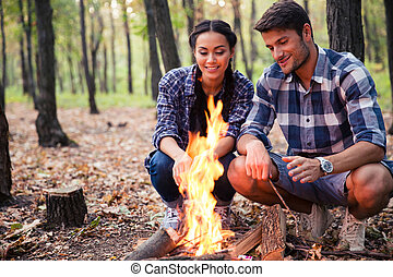 Couple and bonfire in the forest - Happy beautiful couple...