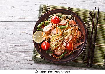 Thai green papaya salad with shrimp. horizontal top view -...