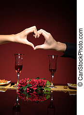 couple at restaurant table making a heart with theyr hands -...
