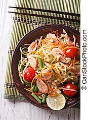 Thai green papaya salad with shrimp close-up. vertical top...