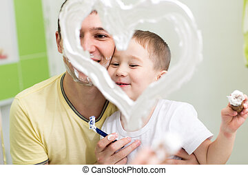 Father and child son drawing heart shape on mirror with...