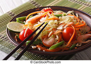 Papaya salad som tam with shrimp close-up on a plate...