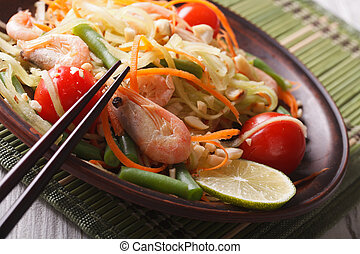papaya salad som tam with shrimp on a plate macro,...