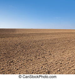 Plowed field - Agricultural background with plowed field and...