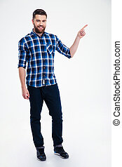 Full length portrait of a casual man pointing finger away...