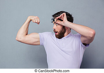 Man looking at his biceps with delight - Potrait of a man...