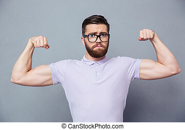 Casual man in glasses showing his biceps - Portrait of a...