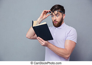 Amazed casual man reading book - Portrait of amazed casual...
