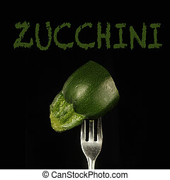 Zucchini on a fork - Zucchini piece on a fork on a black...