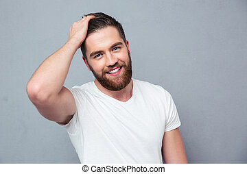 Portrait of a smiling casual man standing over gray...