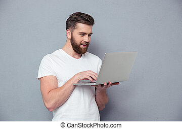 Smiling casual man using laptop computer - Portrait of a...