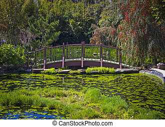 Japanese garden featuring a green bridge over a pond
