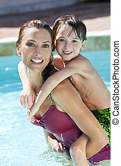 Mother With Son On Her Shoulders In Swimming Pool