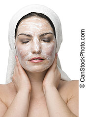 Woman face cream mask - Young woman in white bath towel...
